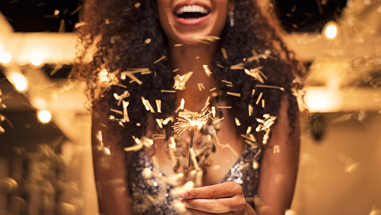 woman holding lit sparkler