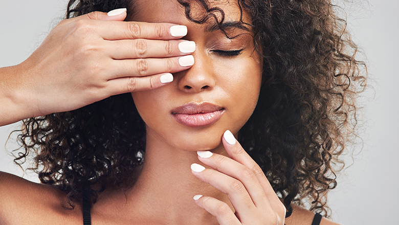close up photo of a woman with hands on face