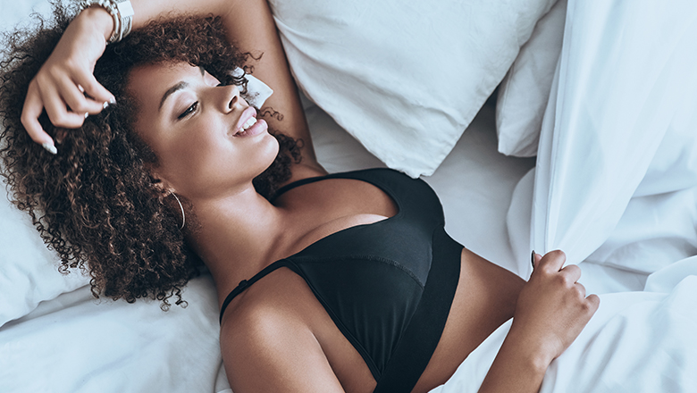 smiling woman lying in bed wearing black bra