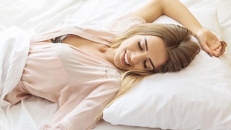 happy woman lying in bed