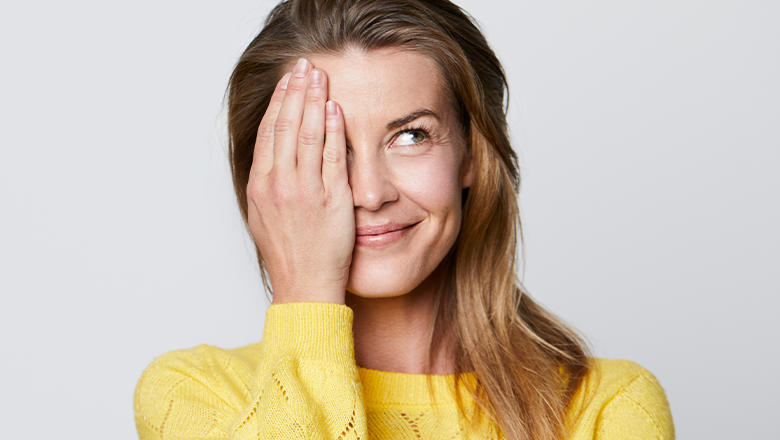 smiling woman with hooded eyelids covering one eye with hand